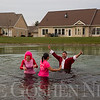 JAY YOUNG | THE GOSHEN NEWS<br /> Waterford Crossing executive director Chad Knisley raises his arms in the air in celebration after he, Kay Hershberger, left, and Alyssa Reyes took a polar plunge into the freezing water of the pond on the Waterford Crossing Campus Wednesday afternoon. The trio made the jump into the freezing cold water for charity. While an exact number was unavailable, at least $1000 was raised by the event. The proceeds from the event will go to The  Window.