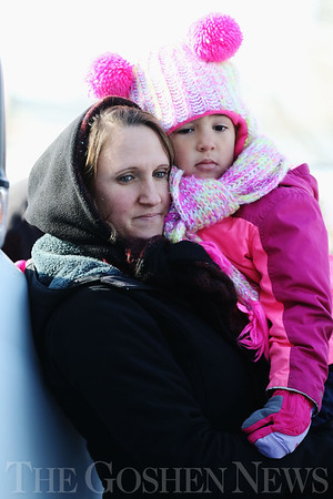 JAY YOUNG | THE GOSHEN NEWS<br /> Jessica Fehr, of Wakarusa, holds her three-year-old daughter Mahayla as they two watch Mahayla's grandmother compete in the ice carving competition during the annual Ice Festival in Shipshewana on Wednesday.