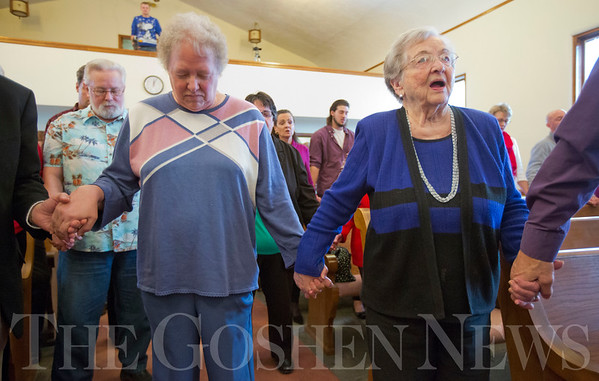 JAY YOUNG | THE GOSHEN NEWS<br /> Janet Benson, left, of Chicago, and Phyllis Grey, of Greencroft, join hands across the aisle with other members of the congregation during a Christmas day service at Forks Mennonite Church on Sunday. After 159 years, the church is shutting down.