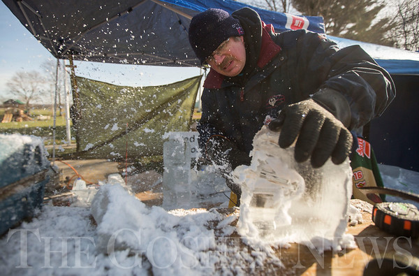 JAY YOUNG | THE GOSHEN NEWS<br /> Ice shavings fly everywhere as Richard Biggs, of South Bend, works on carving a football helmet into ice during the annual Ice Festival in Shipshewana on Wednesday.