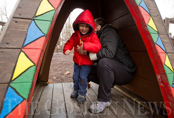 JAY YOUNG | THE GOSHEN NEWS<br /> Three-year-old Micah Holsopple, of Durham, N.C. grins while he and his grandmother Mary Yoder Holsopple, of Goshen, take cover inside the playground equipment at Shaklin Park on Monday afternoon while playing a game of hide and seek. The pair were hiding from Micah's parents, Zeb and Sarah Holsopple, of Durham, N.C., his aunt, Asha Holsopple, of Denver, Colo., and his grandfather, Elroy Holsopple, of Goshen. The group braved the rain to enjoy Monday's unseasonably warm temperatures. The warm weather is not expected to last, as the National Weather Service forecasts tomorrow's high to be 32 with 15mph winds.
