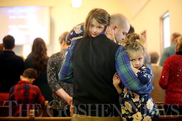 JAY YOUNG   THE GOSHEN NEWS<br /> Shipshewana resident Ryan Yoder holds his daughters Hadley, 5, left, and Harper, 3, during a Christmas day service at Forks Mennonite Church on Sunday. After 159 years, the church is shutting down.