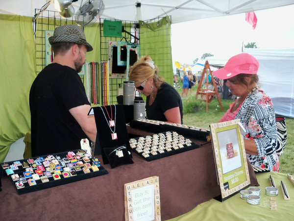DENISE FEDOROW | THE GOSHEN NEWS<br /> Fort Wayne residents Shelly Shank (left) and her mom Bev (right in pink) were first-timevisitors to the Amish Acres Arts&Craft Festival on Friday and wereenjoying visiting the exhibitor's booth, including this one selling jewelry madefrom old Scrabble tiles.