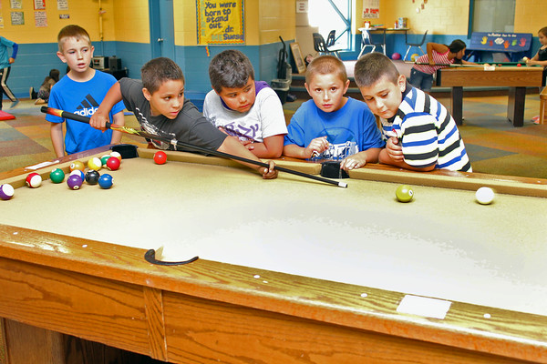 Roger Schneider | The Goshen News<br /> ELIJHA BIRTHA watches his billard shot in the recreation room at the Goshen Boys & Girls Club Wednesday. Club officials are attempting to raise $1.4 million to expand the facility's cafeteria and kitchen. Another fundraiser will be held in the future to expand the education center at the club. Looking on are Allix Brown at left, and then Kevin Lopez, Donta Parker and Serjio Esquibel, to the right of Birtha.