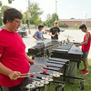 SAM HOUSEHOLDER | THE GOSHEN NEWS<br /> Goshen High School percussion members, from left, Sam Peeler, Matthew Schrag, Oscar Peterson-Veatch and Emanuel Contreras, all sophomores, practice under the shade of a tree Wednesday at the school.