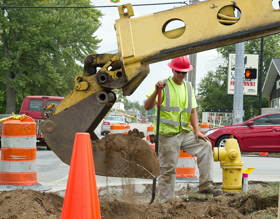 SAM HOUSEHOLDER | THE GOSHEN NEWS<br /> Justin Neulieb, of Hawk Enterprise, watches as a co-worked uses an excavator to dig a hole at the intersection of Lincoln and Chicago avenues Thursday in Goshen. The City Engineering Department said at the Goshen City Council retreat Tuesday that six city intersections including the one pictured would receive signalized American with Disabilities Act compliance improvements. Other intersections receiving improvements are Second Street and Lincoln Avenue, Third Street and Lincoln Avenue, Third and Washington streets, 15th Street and College Avenue and Greencroft Drive and College Avenue.