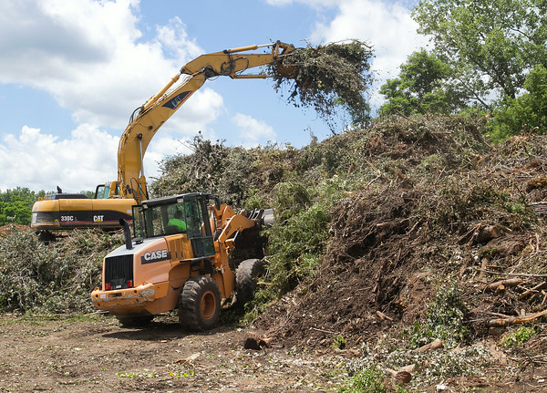 SAM HOUSEHOLDER | THE GOSHEN NEWS<br /> Brush is moved and stacked at the Goshen Environmental Center on C.R. 19 Tuesday. The pile has nearly doubled in size over the last week with brush from the storms being moved out to the center.