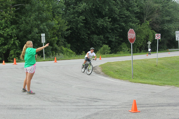 JOHN KLINE | THE GOSHEN NEWS<br /> Volunteer Katie Younghans, left, directs a bicyclist into Shanklin Park as part of the annual Goshen Kids' Try-athlon Saturday morning.