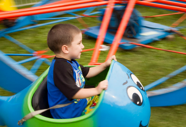 SAM HOUSEHOLDER | THE GOSHEN NEWS<br /> Quinnten Webb, 3, of Elkhart, enjoys a ride at Congdon Park Friday during Bristol Homecoming. The festival's theme this year was Winter in July.