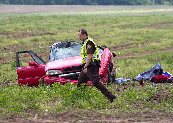 SAM HOUSEHOLDER | THE GOSHEN NEWS<br /> An Elkhart County Sheriff's Deputy walks past a one-vehicle crash Monday on C.R. 44 just east of C.R. 13, south of Foraker. Two passengers in the vehicle were transported by helicopter to South Bend Memorial Hospital, according to police.