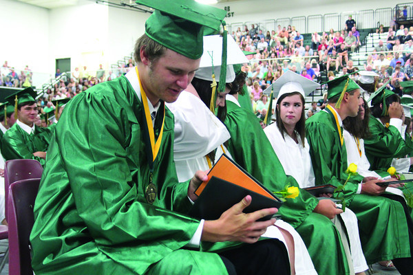 SHERRY VAN ARSDALL | THE GOSHEN NEWS<br /> At left, 2014 senior Nathaniel Trott looks at his diploma during the commencement at Wawasee High School Saturday.