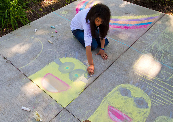 "SAM HOUSEHOLDER | THE GOSHEN NEWS<br /> Keyline Guillen, 11, of Elkhart, draws a minion, from the popular movie ""Despiciable Me"" on the sidewalk outside the Elkhart County Courthouse Friday during First Friday."