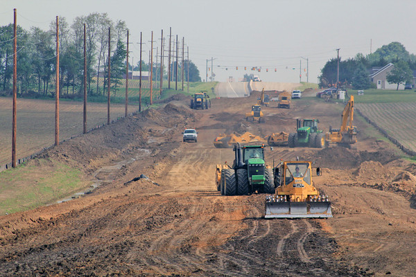 Roger Schneider   The Goshen News<br /> CONSTRUCTION WORKERS operate heavy equipment along the extension of C.R. 17 west of Goshen. The photo is looking north from C.R. 40. Elkhart County Commissioners approved a payment of $700,00 to help fund the work and also straighten curves on C.R. 40.