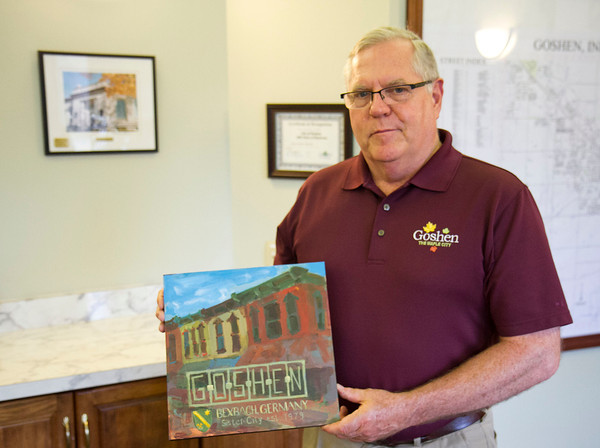 SAM HOUSEHOLDER | THE GOSHEN NEWS<br /> Goshen Mayor Allan Kauffman holds up the painting made by Goshen artist Ben Stutzman that will be given to the city of Bexbach, Germany during a visit this month. Bexbach has been Goshen's sister city for 35 years.