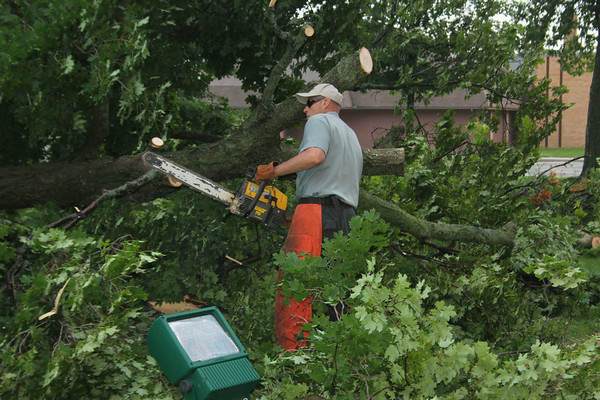 MICHAEL WANBAUGH | THE GOSHEN NEWS<br /> Myron Vanderworth of the Elkhart County Buildings and Grounds Department, cuts up a large maple tree on the lawn of the Elkhart County Courthouse that was toppled during Tuesday morning's storms.