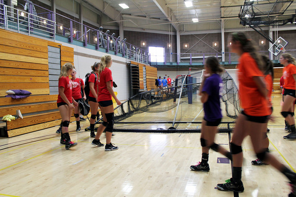 Roger Schneider | The Goshen News<br /> HIGH SCHOOL VOLLYBALL PLAYERS scramble to retrieve their gear from around the gym after their league night was canceled at Goshen College when a suspended baseball and softball bating cage fell on players and spectators. Teh cage can be seen in the background.