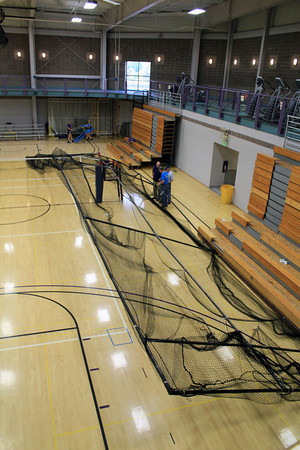 Roger Schneider | The Goshen News<br /> GOSHEN COLLEGE officials examine a batting cage that fell from the ceiling on the east end of the Recreation and Fitness Center Monday night. The cage struck fans in the two sections of stands to the right, but those transported to the hospital were in the stands in the background.