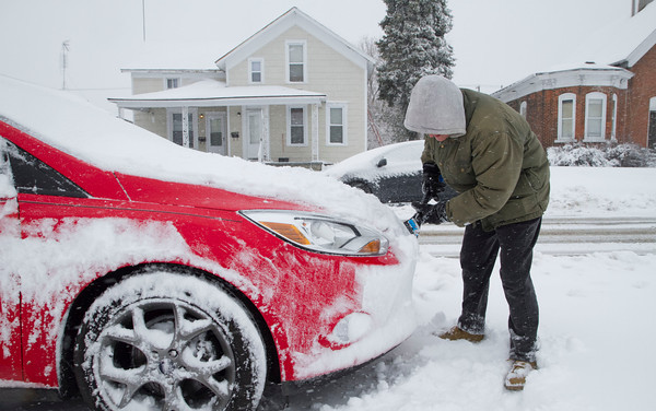 SAM HOUSEHOLDER | THE GOSHEN NEWS<br /> Sheila Moore, of Goshen, clears off her roommate's car on Third Street Wednesday in Goshen. About six inches of snow fell overnight Wednesday into the afternoon, dragging the winter on for another day causing travel headaches and more school cancellations.