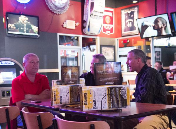 SAM HOUSEHOLDER   THE GOSHEN NEWS<br /> From left, Mike Zent, Mark Miller and Rick Hetler, all of Goshen, watch NCAA Tournament games Friday at Buffalo Wild Wings in Goshen.