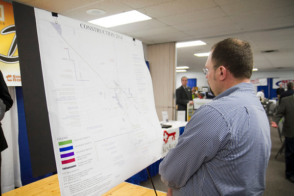 SAM HOUSEHOLDER | THE GOSHEN NEWS<br /> Brad Hunsberger, of LaCasa Inc. looks at a map of proposed road projects in Goshen during the Founder's Day luncheon at the Elkhart County Fairgrounds.