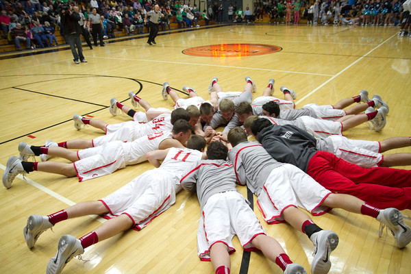 The Goshen boys basketball team huddles up on the court before the Sectional Semifinal game Friday.