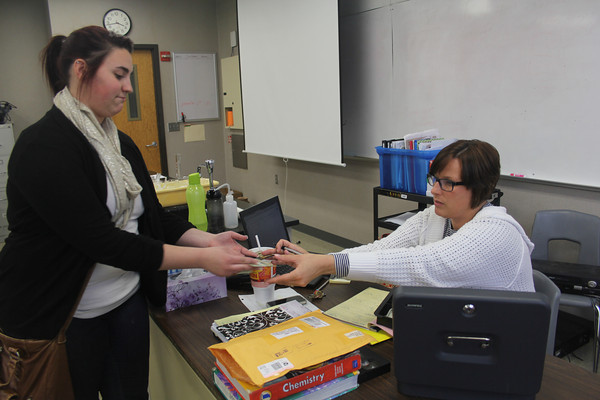 SHERRY VAN ARSDALL | THE GOSHEN NEWS<br /> At right, Goshen High School prom spsonor Cathy Biller hands prom tickets for seniorAbbagail Fowler.