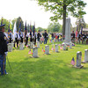 Roger Schneider | The Goshen News<br /> GOSHEN POLICE OFFICER Randy Kantner, left, stands ready during the Goshen Memorial Day ceremony at Oakridge cemetery. The veterans color guard and the Elkhart County Sheriff's Department color guard, are shown in the background at the veterans memorial at the cemetery.