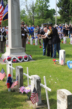 Roger Schneider | The Goshen News<br /> WORLD WAR II Army veteran James Matousek, 93, of Goshen, places the memorial wreath at the veteran's memorial in Oakridge Cemetery Monday morning. Assisting Matousek are Goshen police officers Randy Kantner at right and Jeff Schrock at left.