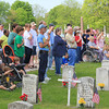 Roger Schneider | The Goshen News<br /> MEMBERS OF THE CROWD at Goshen's Memorial Day service at Oakridge Cemetery salute and hold their hands over their hearts as the national anthem is played.