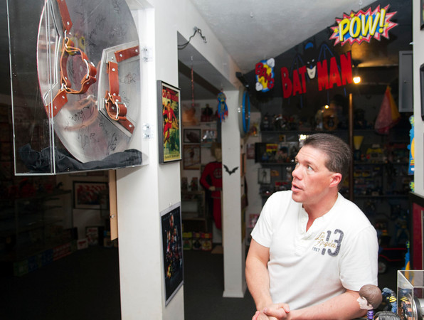 SAM HOUSEHOLDER | THE GOSHEN NEWS<br /> Hall of Heroes owner and curator Allen Stewart looks at the new Captain America shield the museum bought last month. The shield was used in the first Captain America movie and is autographed by the cast of the sequel.