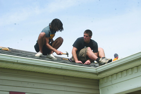 SHERRY VAN ARSDALL   THE GOSHEN NEWS<br /> Goshen College students volunteered their time to put a new roof on the home of Angelina Ram during LaCasa's Annual Help-A-House Community Work Day Saturday.