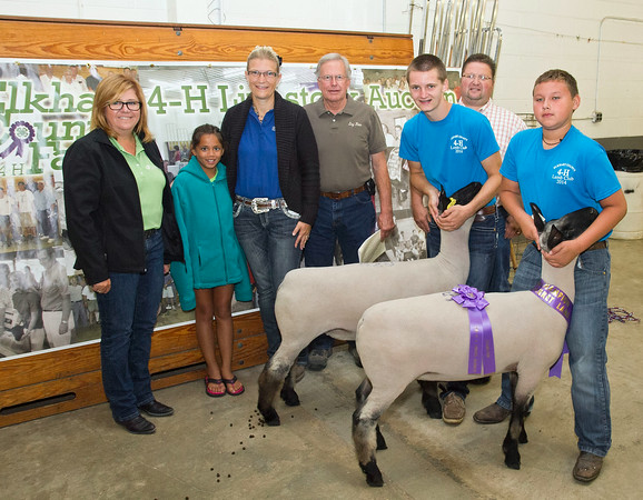SAM HOUSEHOLDER | THE GOSHEN NEWS<br /> Grand champion pen of two lambs belonged to Brandon Lehman, of Topeka, front right. Holding the second lamb, center right is Ethan Bontrager. Buyers include from left, Amy Sink, Interra, Paytoin Smiley, Melissa Lehman, Agronomic Solutions, Gerald Lehman, family of seller, Dr. Paul Webb, of Millersburg Animal Clinic.