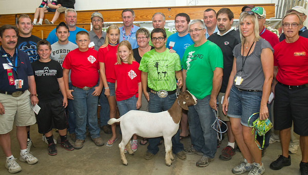 SAM HOUSEHOLDER | THE GOSHEN NEWS<br /> Austin Sanders, center, shows his Grand Champion meat market goat. Buyers in clude, front from left, Michael Christofeno, Drake Risser, Bryce Resler, Madeline Gawthrop, Morgan Gawthrop, Shelly Sanders, mother of seller, Bruce Sanders, father of seller, Dean Gongwer, of Nelson's, Dustin and Bill Mattern of Mattern's Butcher Shop. Back row, from left, Dean Schieber, Mike Getz, of Countyline, Ron George, of Ron George Livestock, Phil Tom, of Turtle Top and Associates, Troy Zahner of National Pedal Pullers and Pushers Racing, Brad Copp of Zahner Farms and Steve Brown, of Wakarusa Sawmill.