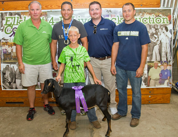 SAM HOUSEHOLDER | THE GOSHEN NEWS<br /> Grand Champion dairy market goat belonged to Caleb Miller, of Goshen. Buyers include, from left, Phil Tom, of Turtle Top and Associates, Steven Edwards, New Paris Telephone and Andrew Hahn of Grand Composites, Miller's father, Myron, is on the right.