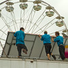 SAM HOUSEHOLDER | THE GOSHEN NEWS<br /> North American Midway Entertainment workers from left, Scottie Reed, John Mareno and Justin Folk take down a carnival game Saturday at the Elkhart County 4-H Fair. The fair finished its eight-day run Saturday.