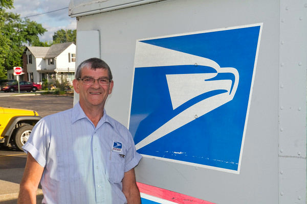 SAM HOUSEHOLDER | THE GOSHEN NEWS<br /> Gary Miller stands next to his postal delivery truck at the Goshen Post Office. Miller is retiring from the USPS after 44 years.
