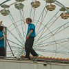 SAM HOUSEHOLDER | THE GOSHEN NEWS<br /> Justin Folk, center, walks across the top of a carnival game while he helps Scottie Reed, take down a sign at the Elkhart County 4-H Fair Saturday. The fair finished Saturday night.
