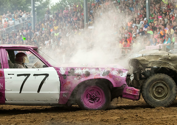 SAM HOUSEHOLDER | THE GOSHEN NEWS<br /> A competitior's car smokes and leaks fluids after it is rammed by an opponent during the demolition derby Saturday at the Elkhart County 4-H Fair.