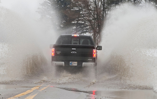 A truck sprays up water as it drives through a flooded Regent Street in Goshen Thursday. Water was flooding many local roadways as melting snow and heavy rain caused drainage issues.