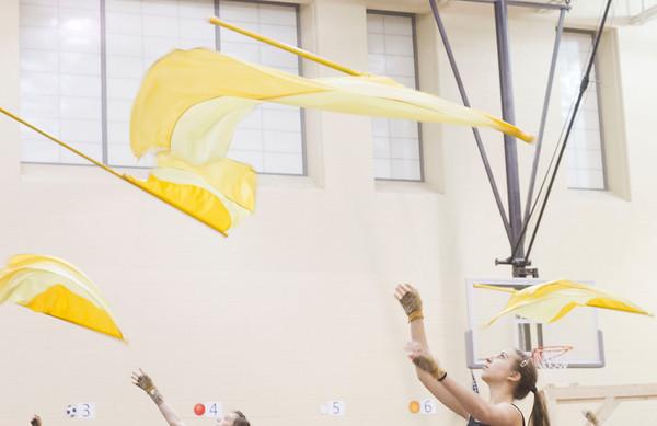 Freshman Kara Pollock twirls her flag in the air during winter guard rehearsal Thursday at Prairieview Elementary School.