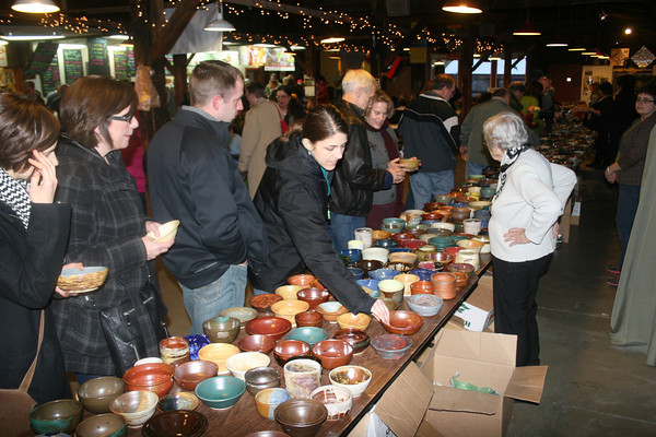 Goshen's Katie Teall, center, searches for the perfect hand-made bowl to fill with soup during Saturday's 13th annual Empty Bowl Project Fundraiser in downtown Goshen.