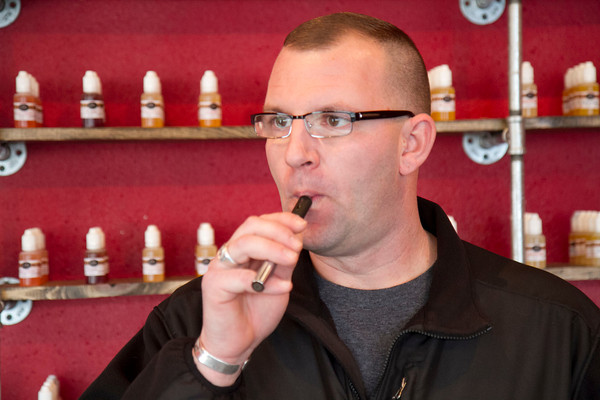 Andy Karnes smokes an e-cigarette at his Nappanee shop Vapor Mills Thursday.