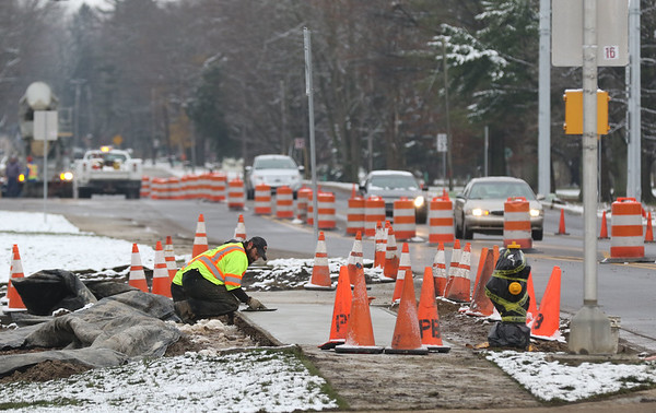 JAY YOUNG | THE GOSHEN NEWS<br /> A worker smooths a fresh concrete sidewalk on the east side of S Main Street near Waterford Elementary School as a line of cars navigate traffic barrels on their way into town Monday morning.
