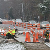 JAY YOUNG   THE GOSHEN NEWS<br /> A worker smooths a fresh concrete sidewalk on the east side of S Main Street near Waterford Elementary School as a line of cars navigate traffic barrels on their way into town Monday morning.