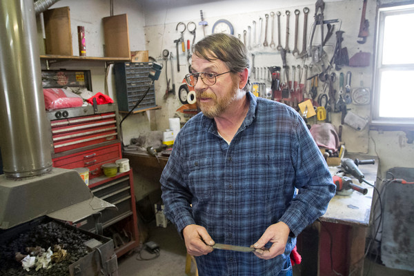 SAM HOUSEHOLDER | THE GOSHEN NEWS<br /> Terry Miller stands in his bladesmith shop in Howe Thursday. Miller makes custom knives and engraves guns by hand using old methods used hundreds of years ago.