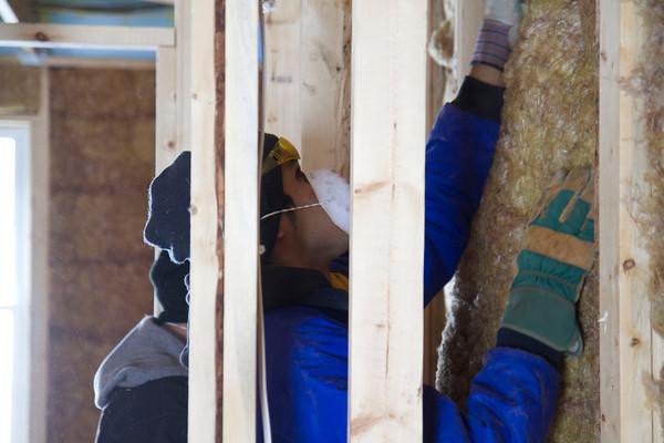 SAM HOUSEHOLDER | THE GOSHEN NEWS<br /> Goshen College freshman Joanlier Hernandez pushes insulation into place at the Habitat for Humanity home in Goshen Wednesday.