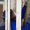 SAM HOUSEHOLDER | THE GOSHEN NEWS<br /> Goshen College freshman Joanlier Hernandez pushes insulation into place at the Habitat for Humanity home in Goshen Wednesday.