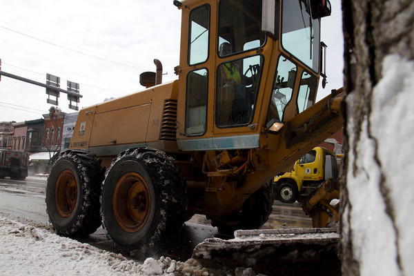 A worker from the Goshen Street Department uses a large grader to clear parking spots along Main Street Sunday as two INDOT snow plows drive down Main Street in the background. The area saw a couple inches of snow overnight Saturday meaning that city streets had to be cleared once again.