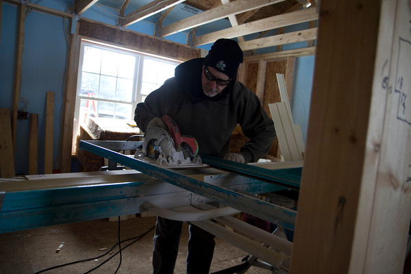 SAM HOUSEHOLDER | THE GOSHEN NEWS<br /> A Habitat for Humanity staffer cuts a piece of wood while working on the house Wednesday in Goshen.
