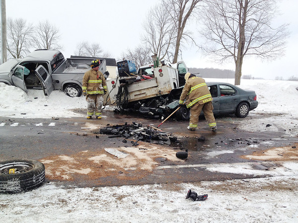 SCOTT WEISSER | The Goshen News<br /> Firefighters and police work at the scen of a multi-vehicle crash north of Nappanee Thursday.